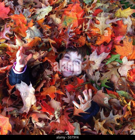 Junges Mädchen in Haufen von Herbstlaub Stockbild