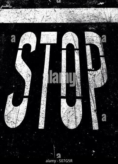 Stop-Schild auf Bürgersteig in schwarz / weiß Stockbild