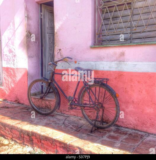 Fahrräder gegen eine rosa lackierte Wand, Kuba. Stockbild
