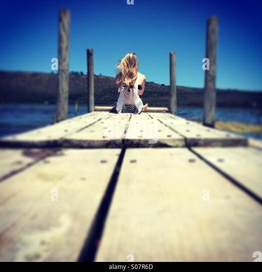 Junges Mädchen sitzt auf einem Steg - Stock-Bilder