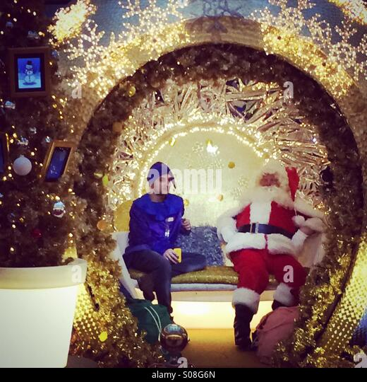 Santa und einer seiner Helfer genießen die Ausfallzeit in einem Einkaufszentrum in London Stockbild