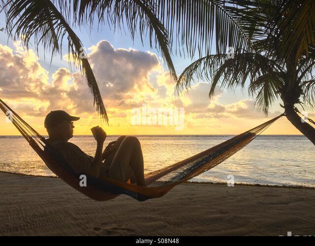 Menschen trinken Kaffee am Strand in der Hängematte, Karibik, Belize Stockbild