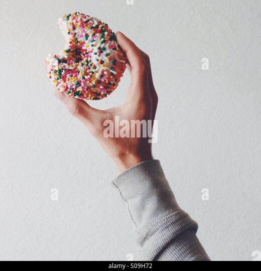 Hält einen Donut mit Streusel Stockbild