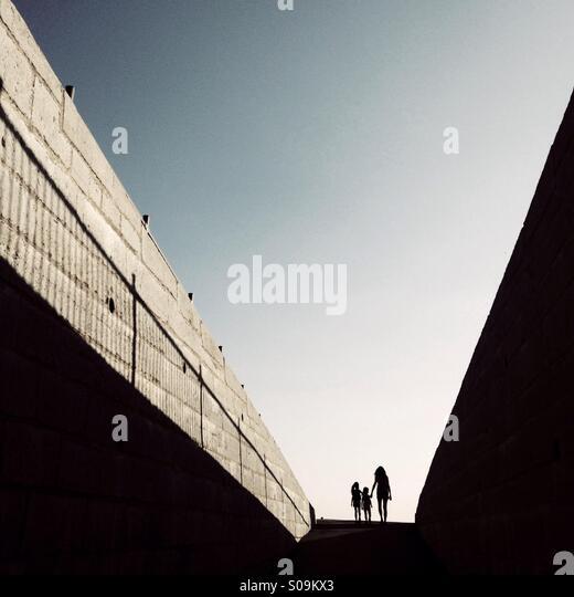Die Silhouette einer Mutter und zwei Kinder am Ende einer langen Rampe. Stockbild