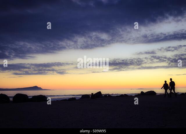 Ein paar Hand in Hand und die Wunder des einen wunderschönen Sonnenuntergang bewundern. Stockbild