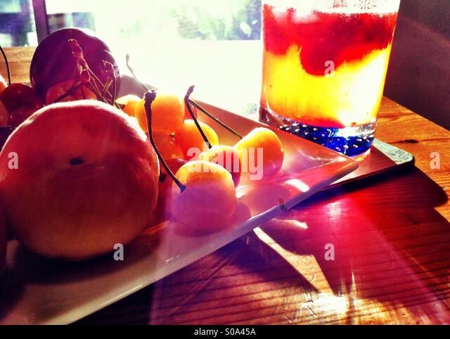 Erfrischendes Sommergetränk in einem Glas auf einem Tisch mit frischen Kirschen und Pfirsich Stockbild