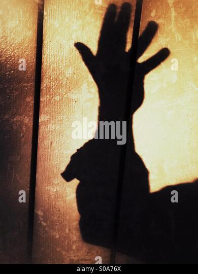 Ein Mann wirft einen Schatten auf die Wand auf seiner Hand zählen. Nummer fünf. Stockbild