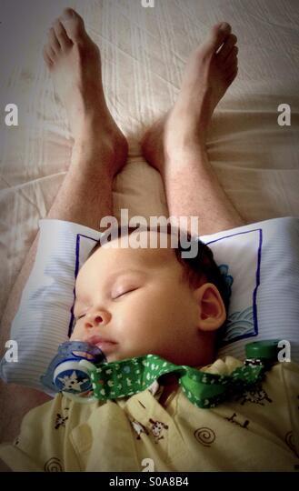 Schöne Babymädchen schlafen auf ihres Vaters Beine Stockbild