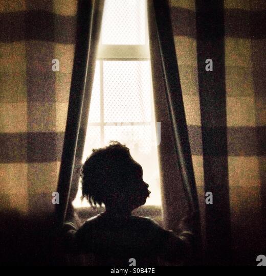 Ein Kind, der Blick durch ein Fenster Stockbild