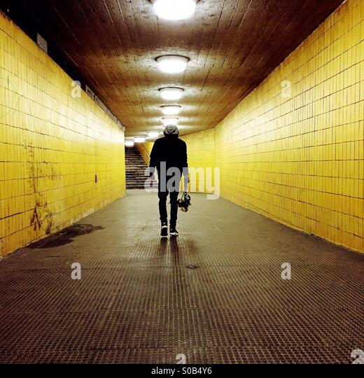 Junger Mann zu Fuß unter einem gelben tunnel Stockbild
