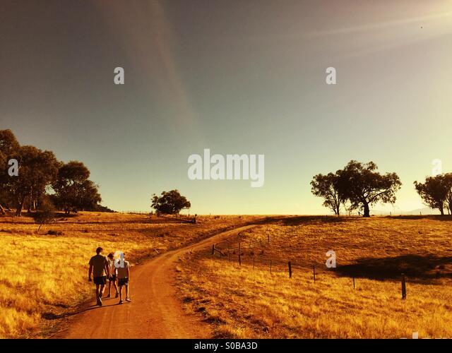 Ein Vater und zwei Söhne Fuß entlang einer Strecke in dem Land in Australien Stockbild