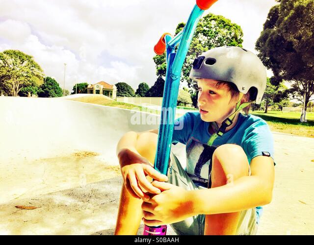 Einen jungen mit seinem Roller im Skatepark Stockbild