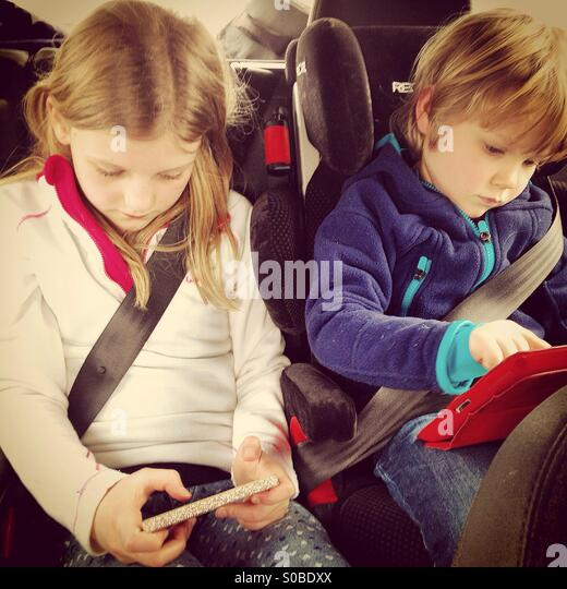 Kinder spielen auf Bildschirmen in einem Auto Stockbild