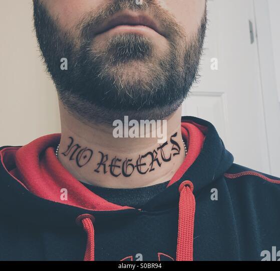 Weißen Männchen mit einem Bart und ein falsch geschriebenes Hals Tattoo tragen einen roten und schwarzen Stockbild