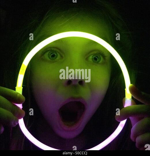 Mädchen, das lustige Gesicht durch Glühen Stick Halskette im Dunkeln suchen Stockbild