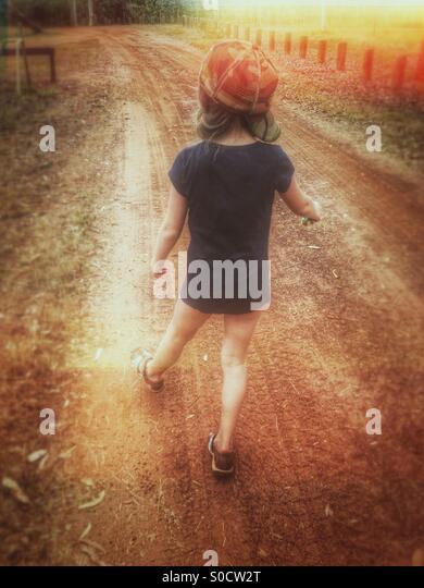 Kleines Mädchen zu Fuß auf einem Feldweg im australischen Outback. Stockbild