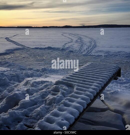 Eine hausgemachte Eisbahn, ein Pier und Ski tracks bei Sonnenuntergang an einem idyllischen Arktis zugefrorenen Stockbild