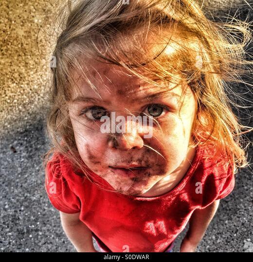 Kind mit einem schmutzigen Gesicht und windgepeitschten Haar nachschlagen Stockbild