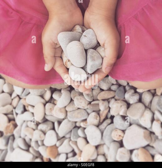 Mädchen die Hände halten Steinen Stockbild