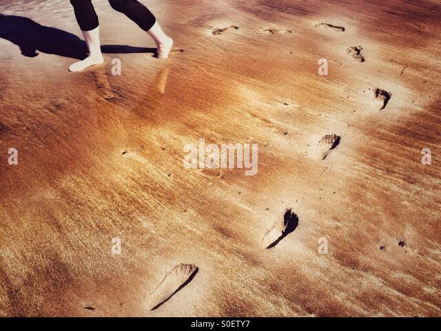 Fußabdrücke, die geschwungene Runde im Sand am Strand Stockbild