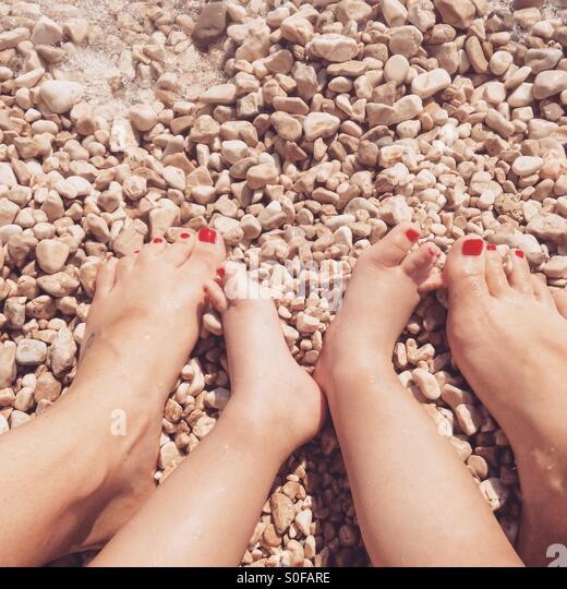 Mutter und Tochter Beine mit roten genagelt Fingern am Strand Stockbild