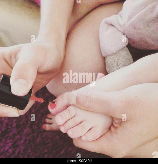 Mutter Tochter Finger roten Nagellack anwenden Stockbild