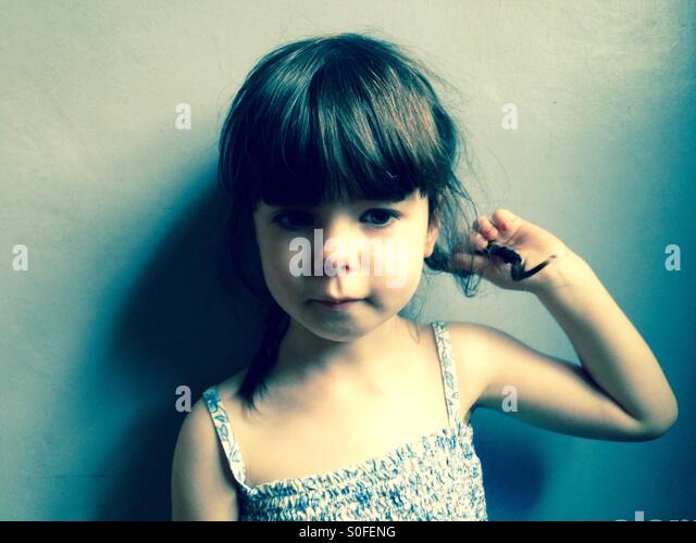 3-jähriges Mädchen spielt mit ihren Haaren Stockbild