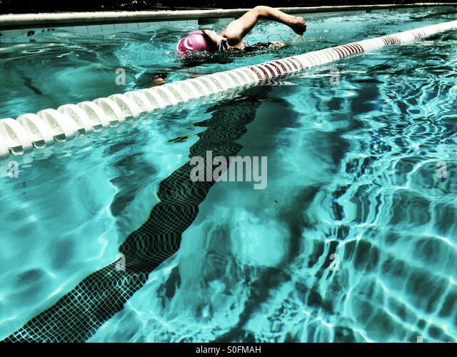Blick vom angrenzenden Gasse, junge Frau, die Freestyle (Australien) Crawl in olympischer Größe außen Stockbild