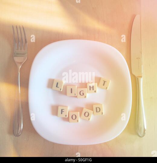 Platte mit dem Scrabble Wörter Licht Essen Stockbild