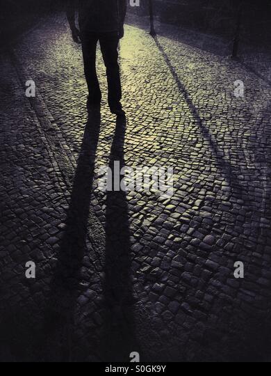 Schattenhafte männliche Figur auf der Straße Stockbild