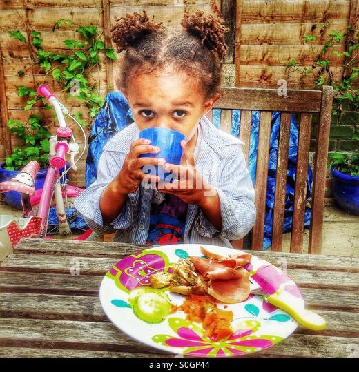 Ein Kind hat eine Mahlzeit im Garten. Stockbild