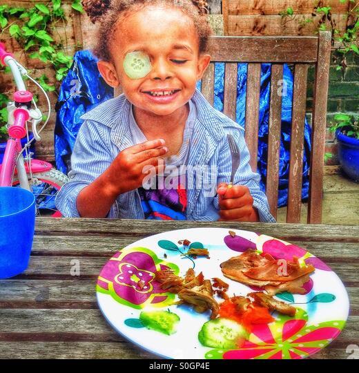 Ein Kind spielt mit Essen im Garten. Stockbild