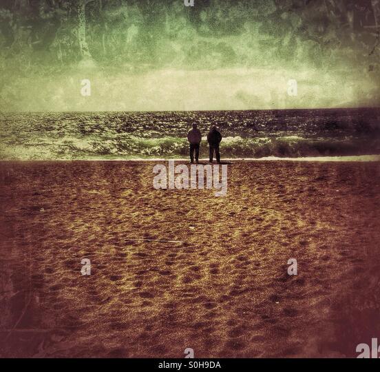 Zwei Touristen am einsamen Strand Stockbild