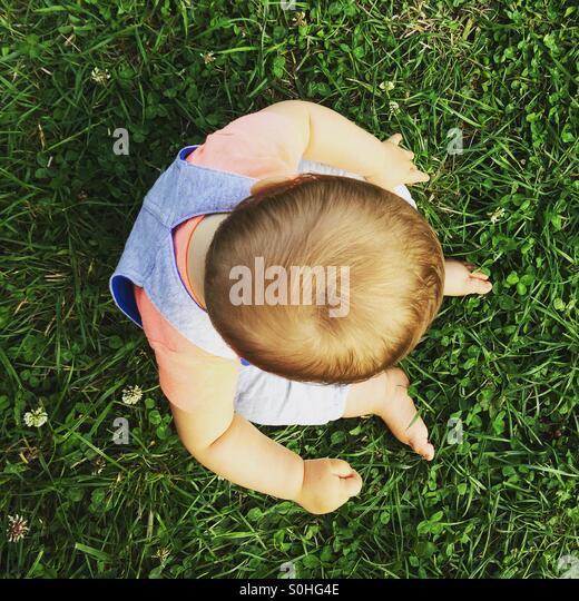 Baby Junge sitzt auf und erkunden Grasgrün Stockbild