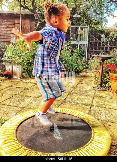 Kind auf einem Trampolin springen Stockbild