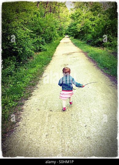Kleinkind läuft ein Rail Trail im Frühjahr Stockbild