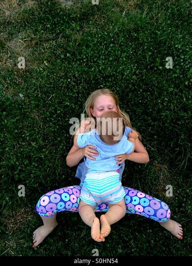Mädchen liegend auf dem Rasen außerhalb mit ihrem Bruder Stockbild