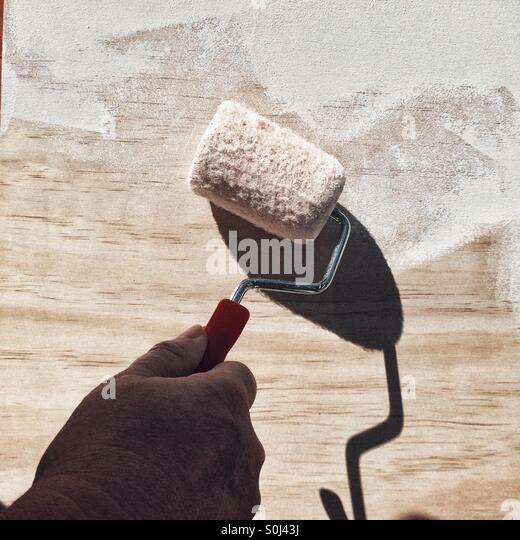 Malen ein Holzbrett mit Walze und weißer Farbe Stockbild