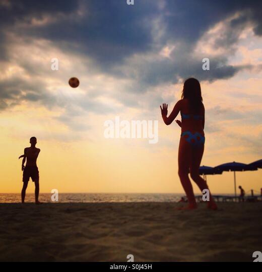 Jungen und Mädchen spielen mit einem Ball am Strand Stockbild