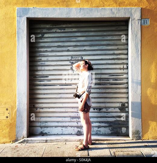 Eine Fotografin mit ihrer Kamera in Arezzo, Toskana, umrahmt von einer verschlossenen Tür. Stockbild