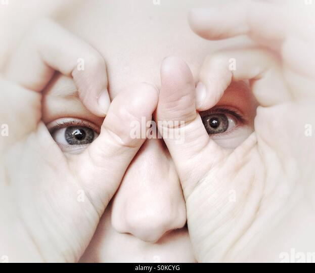 Junge Mädchen auf der Suche durch eine Brille, die von ihren Fingern gemacht Stockbild