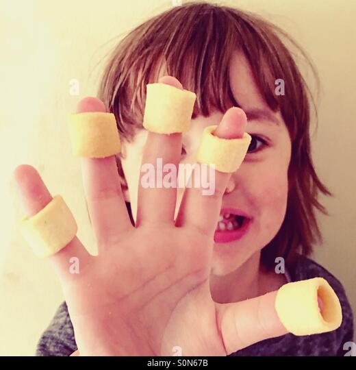 Kleinen 4-jährigen Jungen mit Kartoffelchips an seinen Fingern. Stockbild