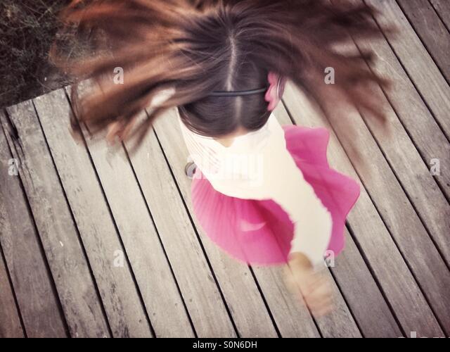 Mädchen in rosa Rock Holz Fuß einschalten Stockbild