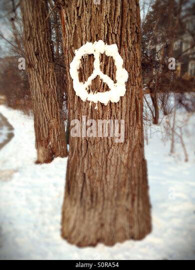 Ein Friedenszeichen aus Schnee auf einem Baum gemacht. Stockbild