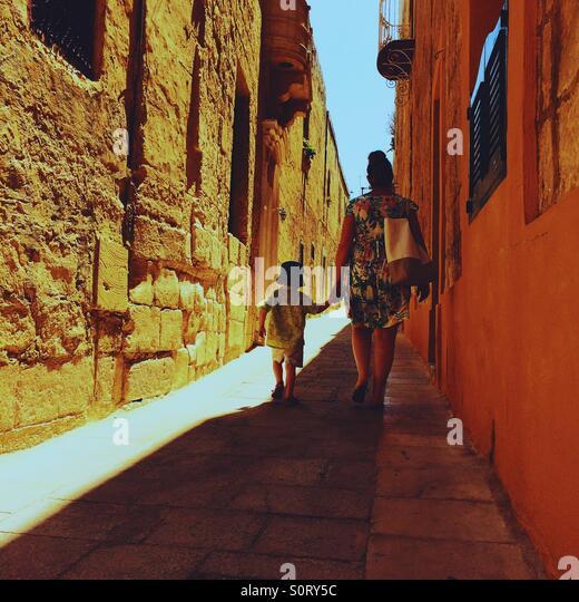 Mutter und Sohn gehen hand in Hand Gasse in Mdina Malta Stockbild