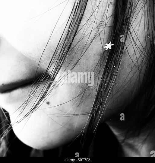 Eine perfekte kleine Schneeflocke in ein Mädchen an den Haaren. Stockbild