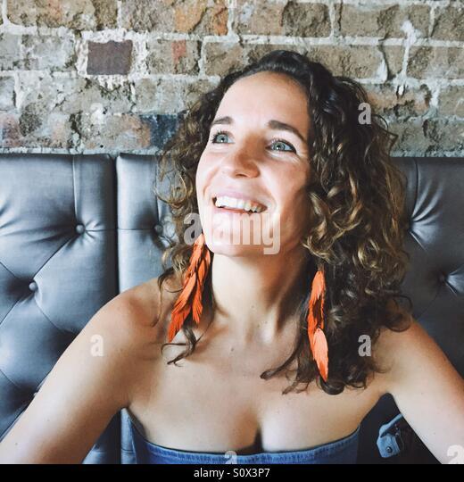 Junge Frau lächelnd und zur Seite schauen Stockbild