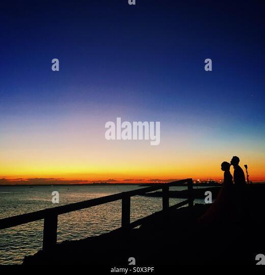 Paar küssen in den wunderschönen Sonnenuntergang Stockbild
