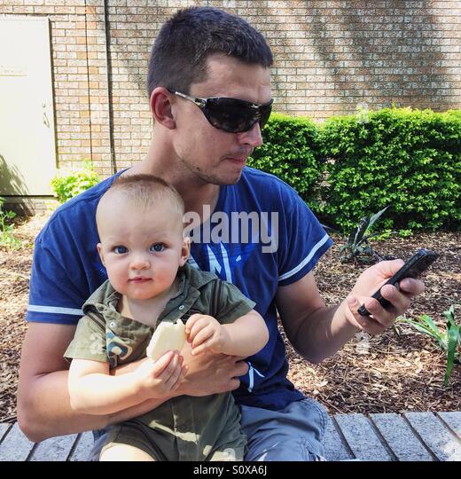 Vater Holding Baby und Blick auf Handy Stockbild