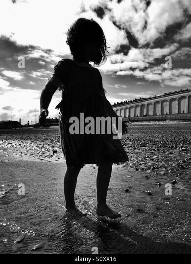 Silhouette der jungen Mädchen am Strand Stockbild